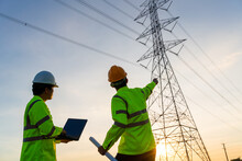 Engineers And Technician Working Inspections At The Electric Power Station To View The Planning Work By Producing Electricity High Voltage Electric Transmission Tower At Sunset