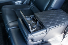 Close-up Of The Rear Armrest With Cup Holders. The Back Row Of An Expensive Car With An Unfolded Armrest. Car Interior Of Luxury Leather Interior Trim With White Diamond Stitching. Car Detail