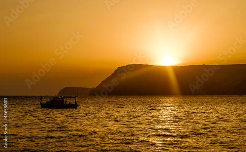 Fotografia A pleasure boat in a quiet bay of the Black Sea in the light of the setting sun