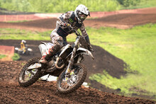 Motorcycle Racer On A Turn. It Rained. Rider Gear And Motorcycle In The Dirt.