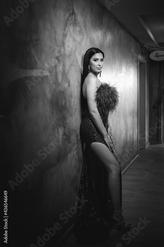 Fotografiet Vertical greyscale shot of a young brunette female posing leaning on a wall in a