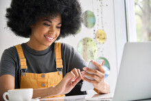 Young Happy Gen Z Black Student Hipster Girl With Afro Hair Sitting At Table In Cafe Indoor Using Mobile Shop Marketing App Online With Computer Working Typing Surfing Internet.