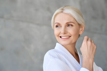 Headshot of happy smiling gorgeous middle aged woman wearing bathrobe at spa salon hotel looking away. Advertising of bodycare spa procedures antiage dry skin care products concept.