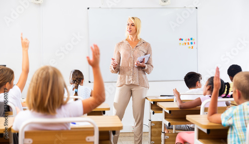 Photo Woman teacher explaining studying material to tweens during lesson in elementary