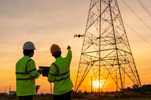 Team Work Of Engineers Location Help Technician Use Drone To Fly Inspections At The Electric Power Station To View The Planning Work By Producing Electricity High Voltage Electric Transmission Tower