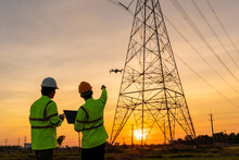 Team Work Of Engineers Location Help Technician Use Drone To Flying Inspect Equipment Instead Of Workers At The High Voltage Electric Transmission Tower, Electric Power Station