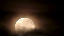 Nighttime Closeup Of Full Moon Rising, While Being Enveloped By Ominous Clouds