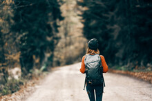 Woman With A Backpack In A Hat And An Orange Sweater On The Road In The Autumn Forest