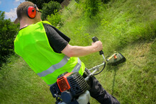 Worker Mowing Grass With Grass Trimmer