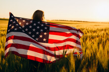 Beautiful Young  Girl With The American Flag In A Wheat Field At Sunset. 4th Of July. Independence Day.