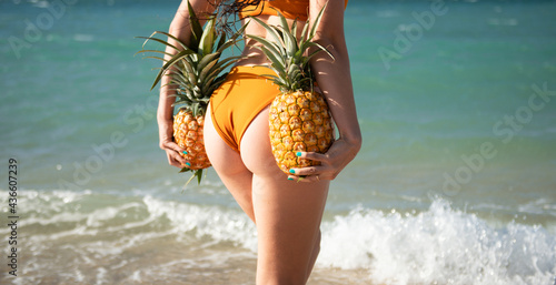 Woman in swimsuit with muscle buttocks hold pineapple near island sand beach Fotobehang