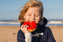 Girl In Delight Eats Donut With Red Icing, Food Stained Her Mouth