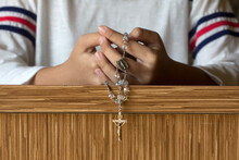 Person Kneeling With Hands Praying Rosary In The Church Background. Catholic Prayer Symbol With Jesus Christ Holy  Cross Crucifix. Believe In God Concept.