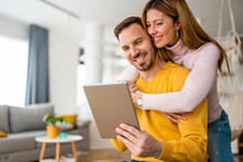 Happy Couple Spending Time With Tablet At Home