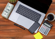 Topview Or Top Down Shot Of Laptop Notebook Computer With Black Coffee In White Cup On Wood Background With Pile Of Dollar Money Banknotes