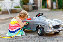 Little Toddler Girl Playing With Big Vintage Toy Car And Having Fun Outdoors In Summer. Cute Child Refuel Car With Water. Girl Using Garden Hose And Fill Up With Gasoline, Role Game Gas Station.