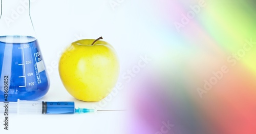 Composition of apple and blue liquid in chemistry flask, with blurred colourful copy space to right