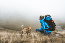 Woman Having Rest In Valley Hugging Dog