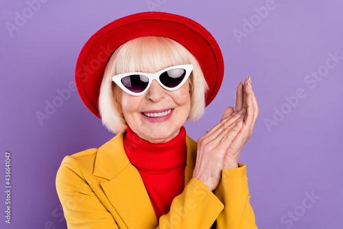 Portait of positive short hairdo aged lady hold hands wear yellow jacket cap eyewear isolated on purple background