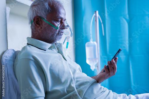 Fototapeta Sick elderly man with on ventilator Oxygen mask checking health status report on