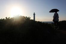 沖縄本島最西端の残波岬灯台と日傘をさす女性