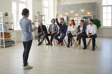 Young Man In Audience Raises Hand To Ask Speaker A Question. Small Group Of People Sitting On Row Of Chairs In Modern Office Space Listening To Business Trainer, Life Coach Or Corporate Psychologist
