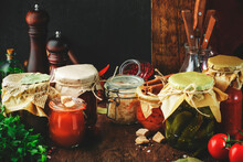 Fermented, Pickled, Marinated Preserved Vegan Food. Organic Vegetables And Fruits In Jars With Spice And Herbs On Black Kitchen Table. Homemade Cunning Concept