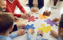 Collaboration Concept. Diverse Multiethnic People Group Team Assembling Jigsaw Putting Puzzle Pieces Together Sitting At Round Office Desk Table Represent Team Support During Coaching Training