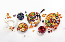 Muesli Bowl And Organic Ingredients For Healthy Breakfast. Granola, Nuts, Blueberry, Cranberry, Oatmeal, Greek Yoghurt, Whole Grain Flakes On White Table