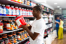 Glad Focused Muscular African Man Choosing Sports Nutrition Products In Shop, Reading Content Label