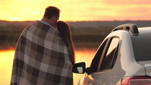 Happy Couple In Love, Travelers Man, Woman Cover Themselves With Blanket Next To Car And Admire Beautiful Sunset On Beach. Tourists Next, Hugging, Admiring Sunrise At Sea. Free Travelers. Travelling