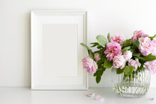 Indoor Image Of Pinkish Peony Flowers Arranged In Vase On Table With Vertical Rectangular Photo Frame With Copy Space For Your Picture Or Design. Home, Decoration, Interior And Memory Concept