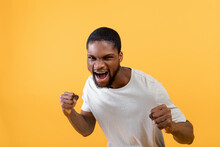 Young Black Man With Fists Defense Gesture, Shouting With Rage, Clenching Fists On Yellow Studio Background