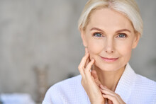 Closeup Of Happy Smiling Beautiful Senior Adult Woman Of 50s Wearing Bathrobe At Spa Hotel Looking At Camera Touching Face. Antiage Spa Procedures Advertising. Skin Care Products Concept. Copy Space.