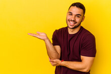 Young Caucasian Man Isolated On Yellow Background Showing A Copy Space On A Palm And Holding Another Hand On Waist.