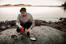 Full Length Of Mature Man Cooking Food On Camping Stove At Lakeshore