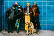 Full Length Of Smiling Men And Women With Dog Against Blue Wall