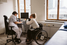 Full Length Of Female Doctor Writing Prescription To Disabled Patient While Sitting At Desk