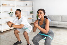 Young Fit Black Couple Training With Elastic Resistance Rubber Band, Doing Squats At Home