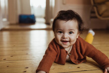 Portrait Of Smiling Male Toddler Lying On Floor At Home