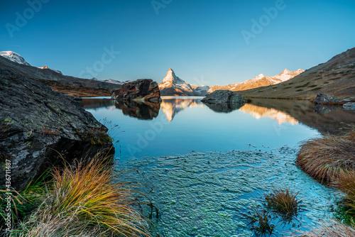 Panoramic morning view of Lake Stellisee with the Matterhorn Cervino Peak in the background. Impressive autumn scene of the Swiss Alps, Zermatt Resort, Switzerland, Europe. #436711487