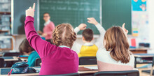 Two Girl Students Raising Hands To Answer A Question In School Class