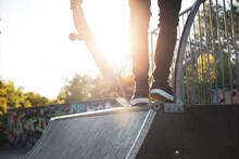 Skater Standing On A Ramp In Skatepark In Sunny Day
