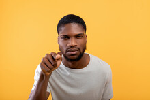 Suspicion Concept. African American Man Gazing And Pointing Finger At Camera, Standig Over Yellow Background