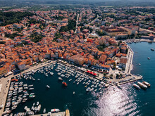 Top View Of The Old Town Of Rovinj, Seaport, Houses With Red Roofs And The Sea, Croatia. The Tiled Roofs Of The Old City Against The Background Of The Bright Blue Sea And Sky, On A Sunny Day