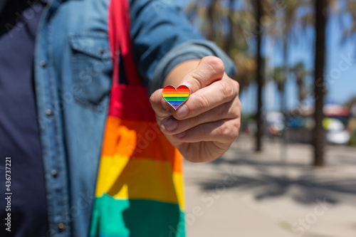 Fotografie, Obraz Man with rainbow reusable bag and lgbt badge, pride month