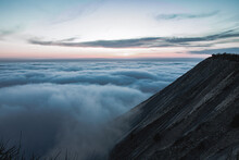 Landscape Of The High Mountains Above Clouds. Lights Of Sunset Touch Forest At Evening Time. Thick Fog Covered Nature.