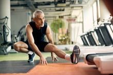 Mature Athletic Man Stretching His Leg While Working Out In A Gym.