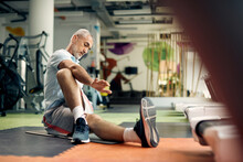 Mature Athletic Man Stretching On The Floor While Exercising In A Gym.