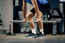 Unrecognizable Mature Sportsman Exercising With Barbell During Strength Training In Gym.